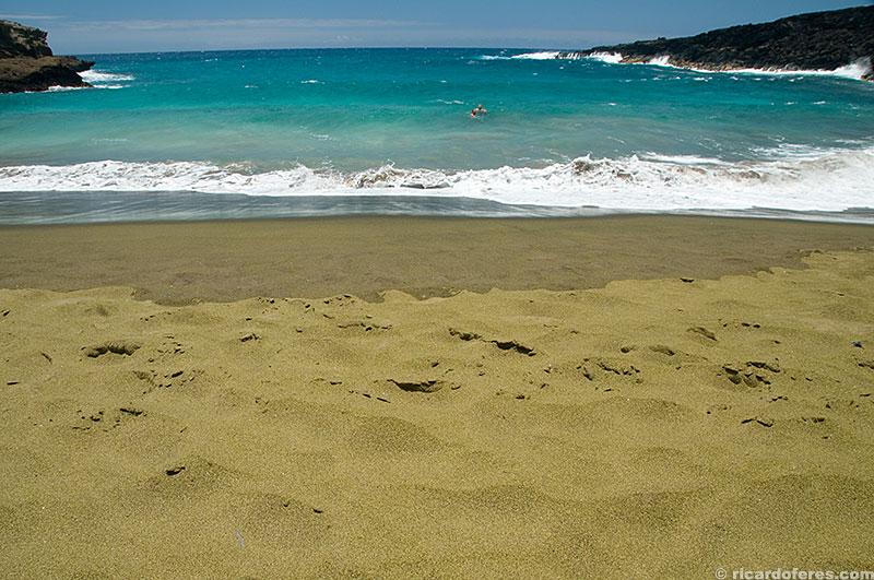 A areia não chega a ser verde, mas a praia é linda independente da cor da areia